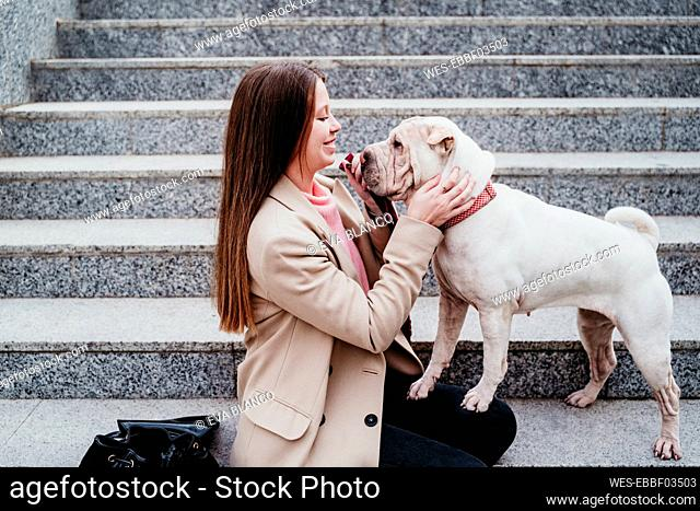 Smiling woman looking at pet while sitting on steps