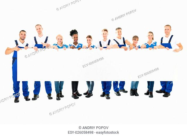Portrait of happy multiethnic cleaners holding blank billboard against white background