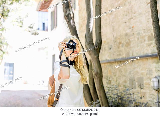 Blond woman photographing with camera