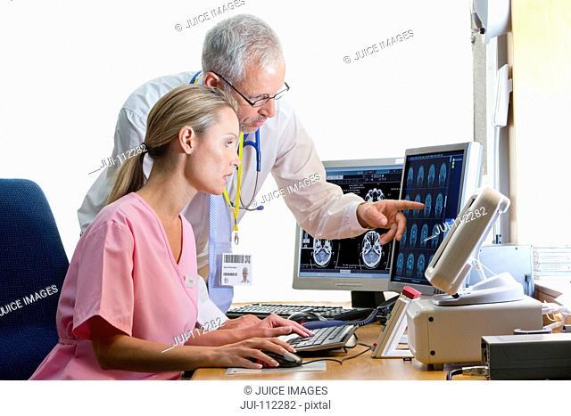 Doctor and nurse reviewing digital brain scan in doctor