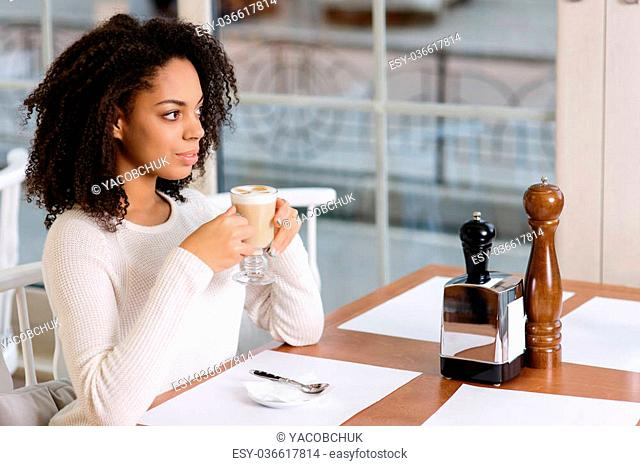 Drinking cappuccino. Young appealing woman enjoying her cup of cappuccino