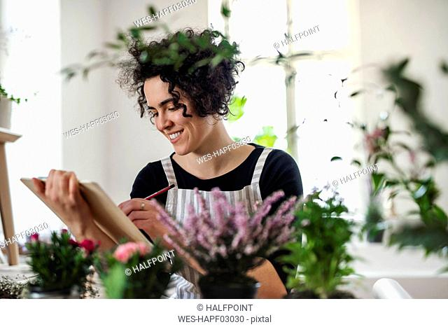 Smiling young woman with clipboard in a small shop with plants
