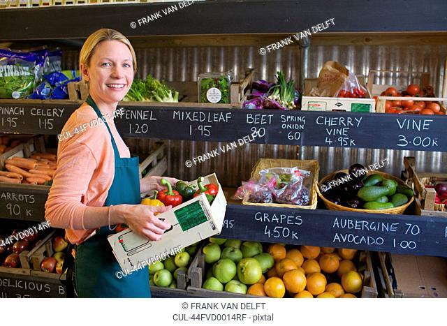 Grocer arranging produce for sale