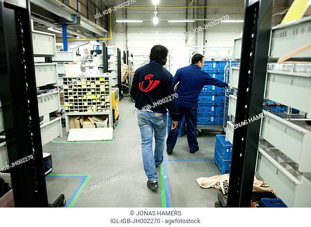 Picture shows belgian post employees as they work in sorting center with postbags filled with certified mail / letters / packages before daily round circuit in...