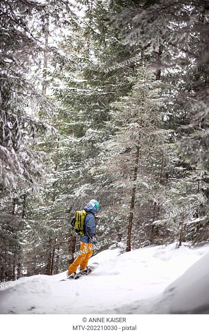Teenage girl with snowboard in snow covered forest