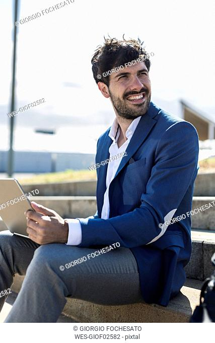 Smiling young businessman sitting on stairs with laptop turning round