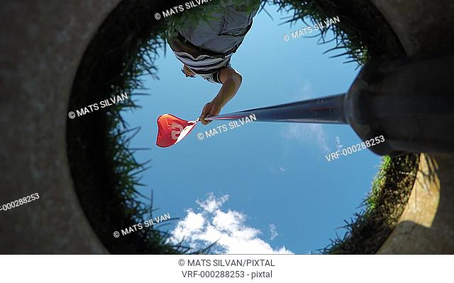 Directly below view on a caddy taking away the flag from the golf hole and the ball falling in to the hole in a sunny day with blue sky in Switzerland