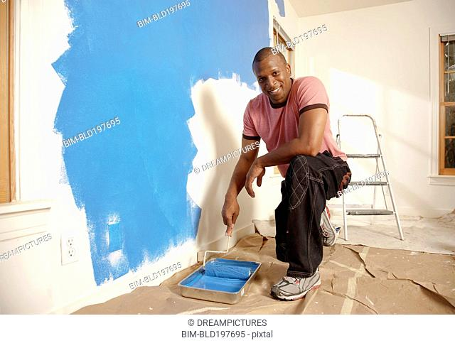 African American man painting wall