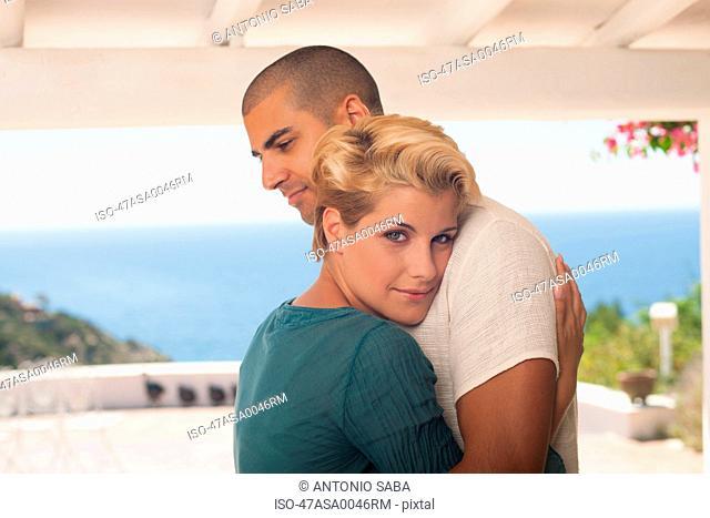 Smiling couple hugging on balcony