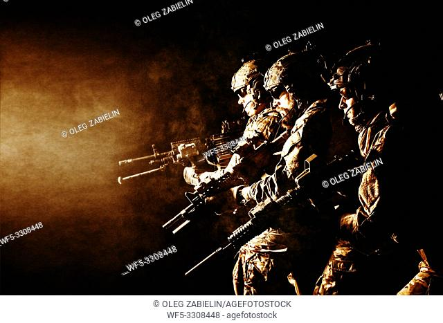 Group of security forces in Combat Uniforms with rifles, lined in the face of danger. Facing enemy, they stand boldly and ready to protect the nation