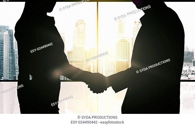 business, teamwork, partnership, cooperation and people concept - partners shaking hands over office window and singapore city skyscrapers background and sun...