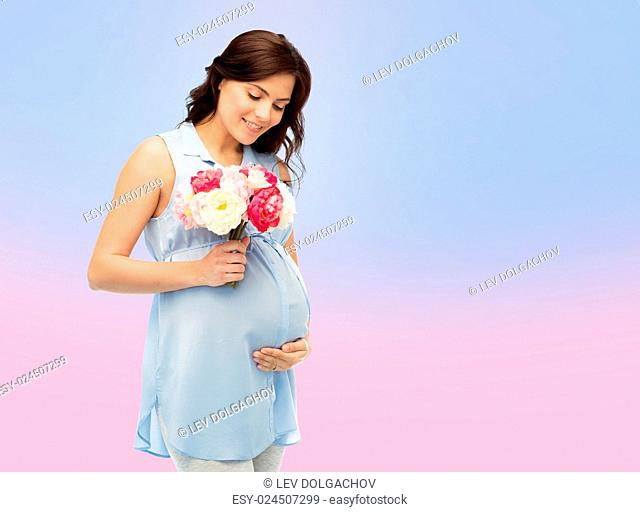 pregnancy, motherhood, holidays, people and expectation concept - happy pregnant woman with flowers touching her big belly over rose quartz and serenity...