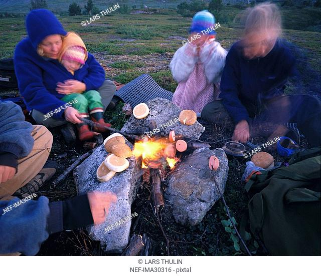 Defocused family sitting at camping fire and baking food