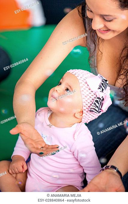 Little baby girl and her mother playing with soap bubbles