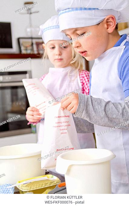 Germany, Girl and boy using baking powder