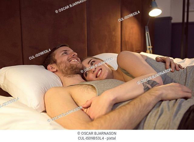 Young couple in bed, hugging, smiling