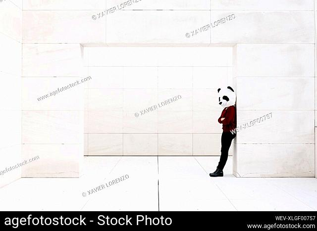 Depressed woman with arms crossed standing at doorway against wall