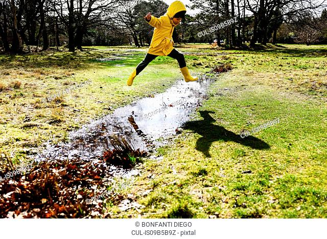 Boy in yellow anorak jumping over puddle in park