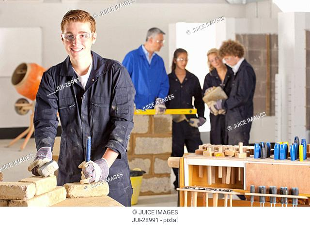 Student with hammer and chisel in bricklaying vocational school