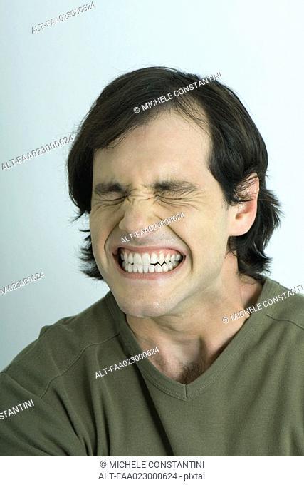 Man closing eyes and clenching teeth, portrait
