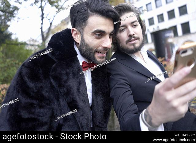 man showing friend content on smartphone