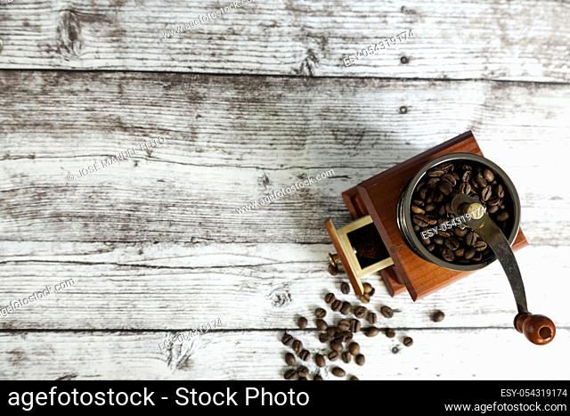 coffee grinder with coffee grains on wooden table from above. Top view