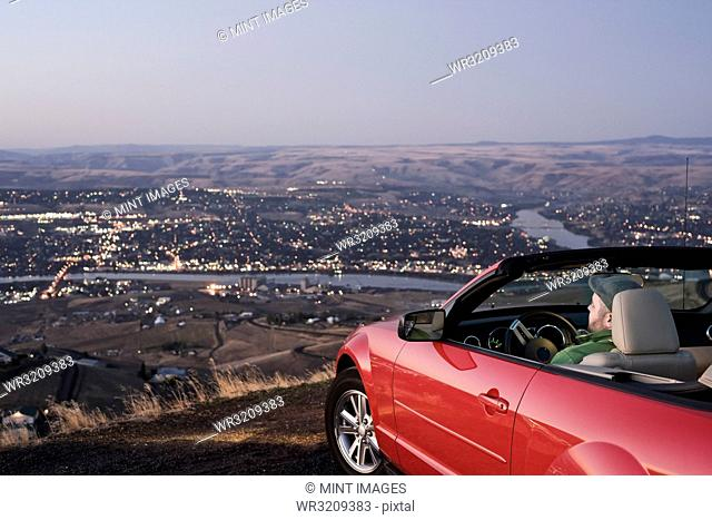 A Caucasian male parked in his convertible sports car watching the sunset over the Clearwater River and the city of Lewiston, Idaho, USA