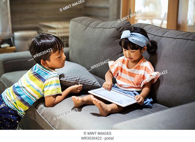 Young girl with black pigtails sitting on a sofa, digital tablet on her lap, boy standing beside her