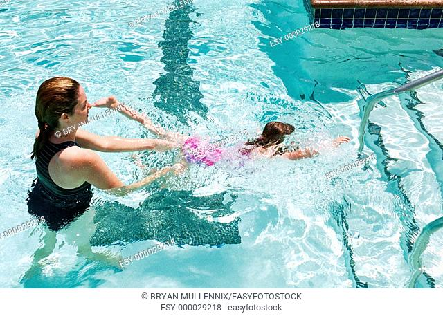 34 year old mother teaching 5 year old daughter to swim