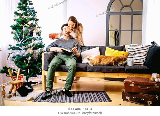 christmas holiday couple happy young woman surprise boyfriend cover his eyes