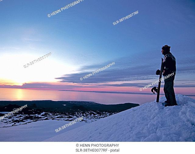 Snowboarder overlooking snowy landscape