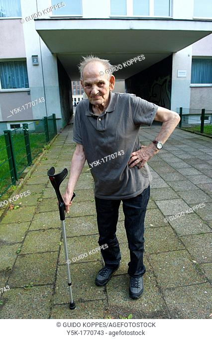 East-Berlin, Germany. Portrait of an old man with cane in front of 'his' projects or 'Plattenbau'