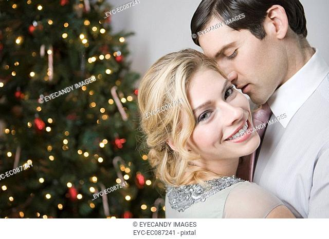 Portrait of young affectionate couple at home on Christmas