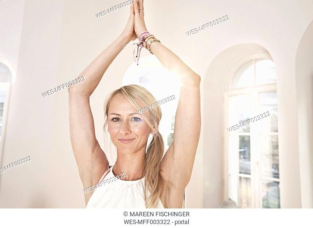 Young woman holding a Vrksasana yoga pose in sunny studio
