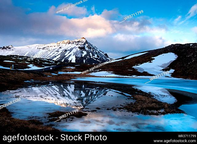 Icelandic landscape with frozen lake and stapafell mountains covered in snow and reflected on water at snaefellsnes peninsula in Iceland