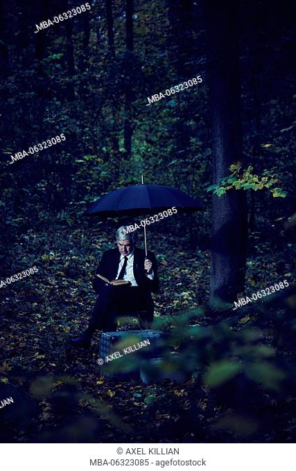 Man is sitting in the forest with umbrella book and two suitcases and is reading