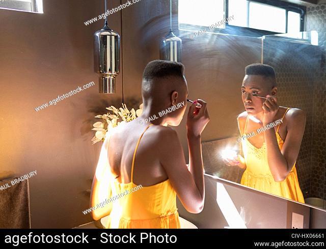 Young woman applying mascara in sunny bathroom mirror