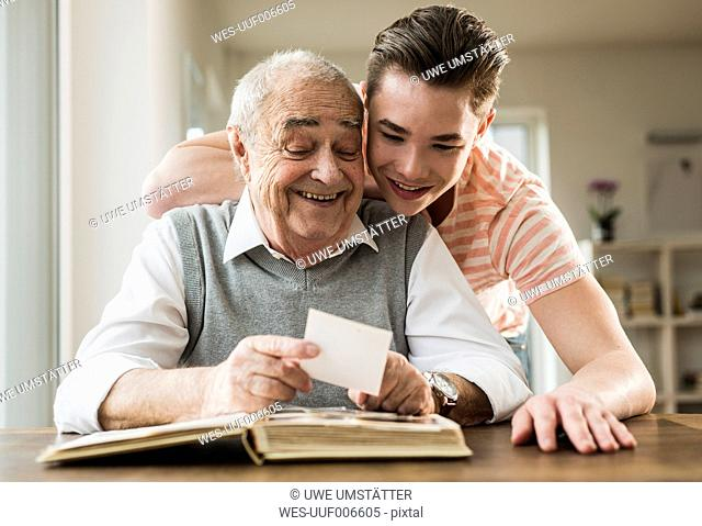 Grandfather and grandson watching old photographies together