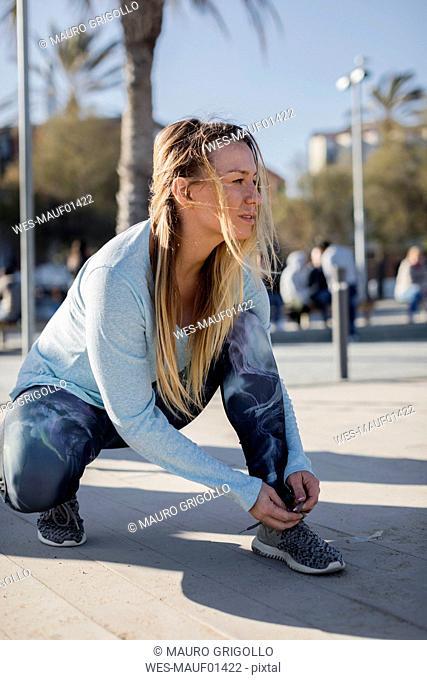 Spain, Barcelona, woman tying running shoe on beach promenade