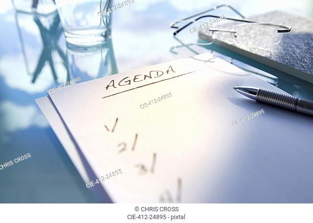 Close up of desk with,glass,glasses and note saying 'agenda',pen