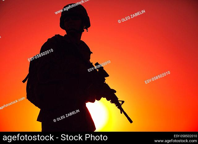 Silhouette of army special forces rifleman, Marines, coast guard or anti-terrorist squad soldier in ammunition and helmet, armed service rifle