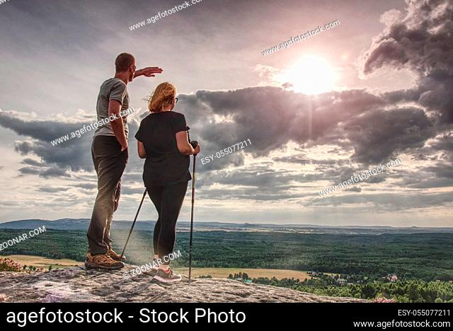 Couple, girl and boy, on hilly path. Both watch in far direction cloudy horizon