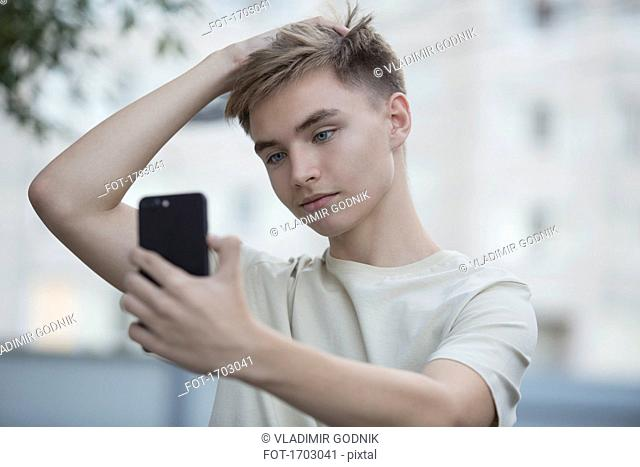 Teenage boy taking selfie from mobile phone with hand in hair