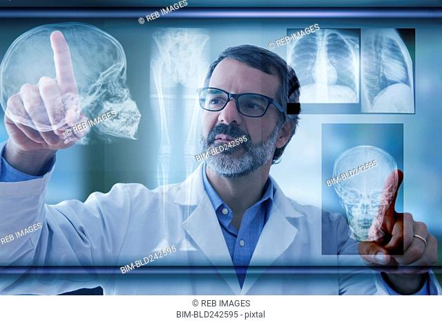 Hispanic doctor examining x-rays on virtual screen