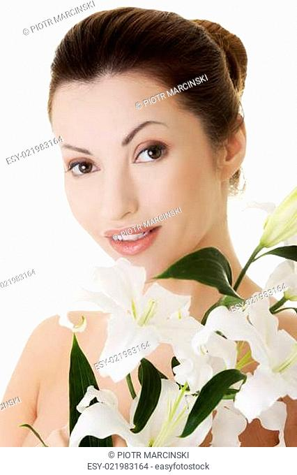Portrait of beautiful adult woman with health skin and with lily flower