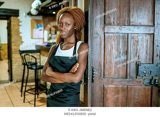 Portrait of young waitress at the door of a bar