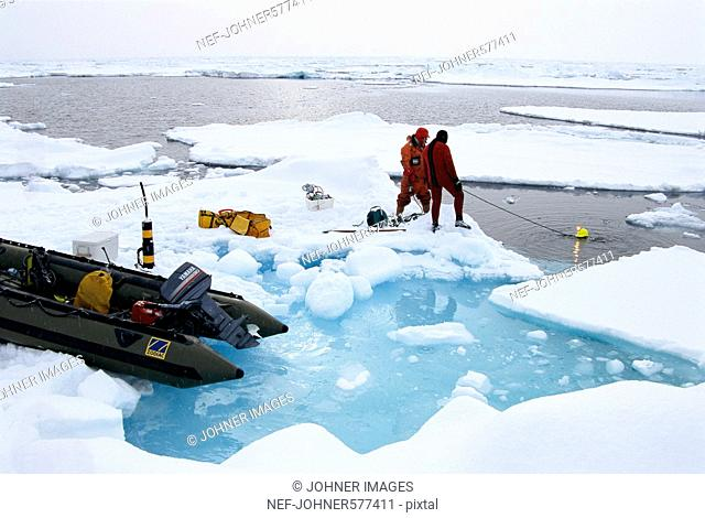Researchers diving under the ice, Svalbard, Norway