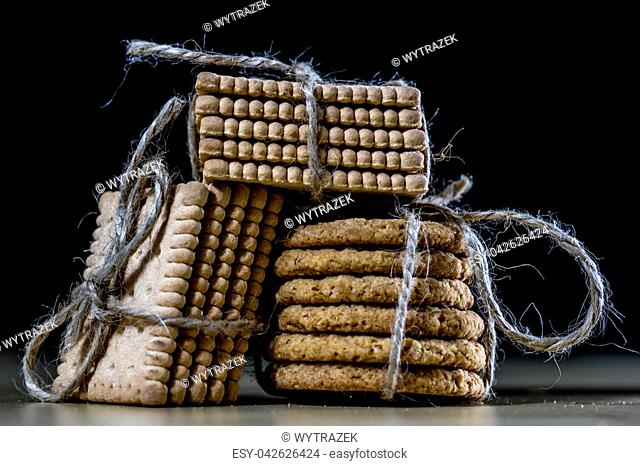 Cookies tied with a gray jute string into a bow. Cookies of sweets on a wooden kitchen table. Black background