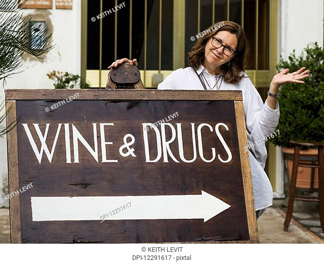 A woman posing with a sign for wine and drugs; Ravello, Italy