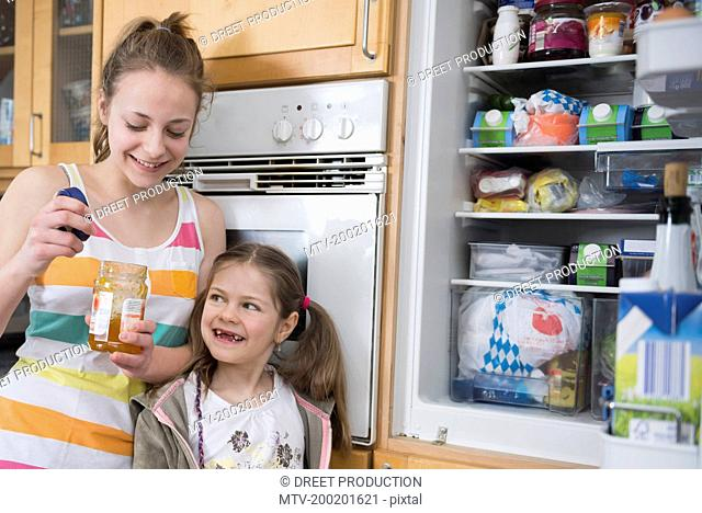 Sisters looking into refrigerators, smiling